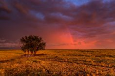 Title:  Fire Within.  A tranquil scene on the Oklahoma prairie of a red sky and a beautiful rainbow.
