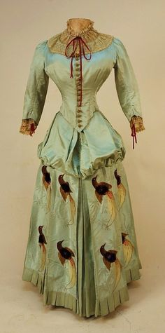 Silk bustle dress, with tufted brocade birds, pale aqua faille, three skirt front panels brocaded with tropical foliage and colorful birds in gold, burgundy, plum, red and brown, having body of tufted silk floss in high relief, pointed boned bodice with embroidered net collar and cuff laced with red ribbon, crocheted buttons, lined in cotton twill, 1880's