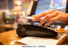 Female electronic payment close-up cell phone hand shop electronic reader - Stock Photo