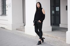 Elisa from the Fashion- and Lifestyleblog www.schwarzersamt.com is wearing a black cold shoulder sweater from H&M Trend, black leather pants from MANGO, mules from GOERTZ and a clutch from AMERICAN VINTAGE. It's a minimal und clean allblack blogger look with white accents.