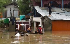 Photo: IFRC. A flood victim taking refuge on roof of a house in Srinagar.