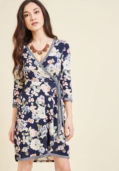 <p>You can find enjoyment in just about anything, but it's the lovely little details of this navy dress that really make you smile! There's joy in a flattering wrap silhouette, but this knit frock takes that pleasure one step further with cropped sleeves, striped accents, and a pretty floral print.</p>