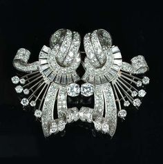 A diamond double-clip brooch, circa 1955,  each clip composed of a brilliant-cut diamond circlet with baguette-cut diamond fringe, issuing a highly stylised scroll set with old brilliant and single-cut diamonds, diamonds approximately 11.50 carats total, length 5.2cm.