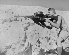 "A New Zealand soldier part of Expeditionary Force ""2NZEF"" firing dual Bren's joined by an AA mount during Operation Crusader in North Africa"