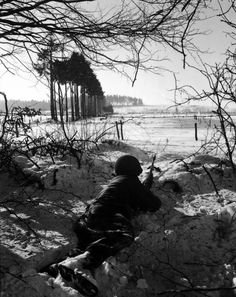 An American soldier waits patiently  in the snow at the ready near St. Vith, Belgium during the Battle of the Bulge (December 1944)