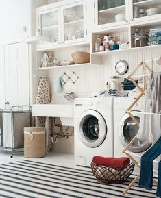 Cottage laundry room features glass-front cabinets stacked over open cubbies on ivory beadboard walls suspended over white porcelain utility sink next to front-load washer and dryer as well as ticking stripe laundry sorter on ivory and black striped rug layered on whitewashed plank floor.