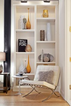"""Rather than jamming shelves full of knickknacks, Eisen opted for a minimalist look: Several books stand upright along with tall vases that fill the space without overcrowding it. She also added objects of various height and color to give the bookcase personality. Her favorite part about decorating this home? """"Turning wasted, unused space into a functional reading nook that can be enjoyed by many by simply adding a chair."""" Steal this look with clusters of tall, affordable vases…"""