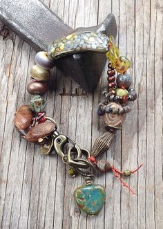 """MarketPlace """"Forest Floor"""": lots of lamp work glass (notice the curved glass focal bead), wood, agate, glass, brass; hand-knotted on orange ..."""