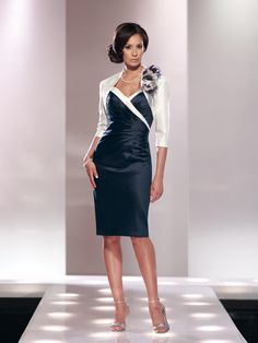 Two-piece shantung suit, sleeveless knee-length sheath with tapered shoulder straps, sweetheart neckline, directionally pleated bodice, center back slit, matching bolero jacket with three-quarter length sleeves and detachable hand-crafted floral pin, suitable for the mother of the bride or the mother of the groom. Sizes: 4 – 20