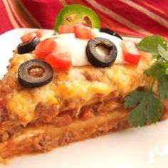 Burrito Pie - Mexican style lasagna with layers of tortillas, ground beef (or chicken), shredded cheese, green chiles, black olives, tomatoes and refried beans and baked until brown and bubbly.