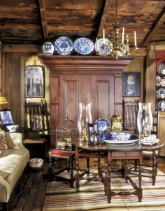 The sitting room makes a cozy repository for a large cast of 18th-century pieces that include a Hudson Valley wardrobe (a kas), an English gateleg table, and a brass lantern clock. Keith Scott Morton.