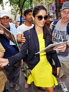 Freida Pinto greets fans in NYC looking uber chic in oversized purple sunnies, a buttercup yellow dress & navy blazer
