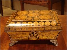 1820 ca.   Gentleman's Glove Box. Sarcophagus shape decorated with penwork Romanized images of British monarchs, plus sides vignettes of significant events in British history, and pressed gilt brass ring handles and feet.