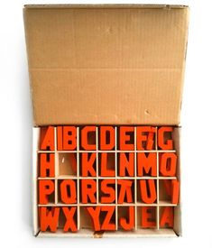 """A box of vintage Creative Playthings letters from 1977.  A complete set of 80 orange wooden letters: 2"""" high, 3 of each letter with an extra A and E, all in the original box."""