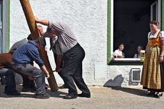 Week of Apr 26-May 2, 2014 A woman watches men raise a May Pole outside of an inn in Grossweil, Germany, on Thursday. (Karl-Josef Hildenbrand/European Pressphoto Agency)