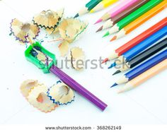 Colored pencils with colorful pencil shavings on white background