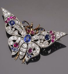 A diamond and gemstone brooch in the form of a butterfly; mounted in platinum and fourteen karat gold; length: 2 1/16in.