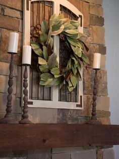 Living Room decor - rustic farmhouse style. Fireplace mantel scape featuring a magnolia wreath over a window frame with tall rustic wood candlesticks. Joanna Gaines of Fixer Upper style.