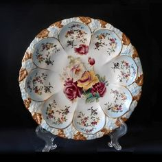 This is a lovely hand painted Reinhold Schlegelmilch porcelain bowl with blue tinting and large handpainted peonies. Each of the eight molded panels contain sprays of small hand painted flowers. It has an embossed floral rim with brown and gilt leaves. It measures approximately 10 inches in diameter and is in excellent condition with no chips, cracks, scratches or wear. The back is marked with a green and red RS within a laurel wreath.