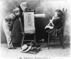 Boy with homemade 'Kodack' camera pretending to photograph little girl with doll, 1907.