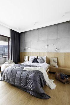 Beton i drewno tworzą efektowny duet na ścianie tej sypialni. Z drewna o tym samym odcieniu wykonano nie tylko podłogę, ale też zagłówek łóżka zintegrowany z szufladami. Kinkiety biurowe na wysięgnikach to świetne rozwiązanie dla osób lubiących czytać w łóżku.