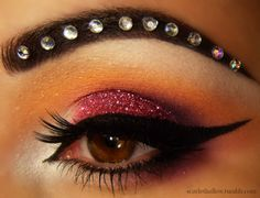 Sparkly burgundy eye shadow with dramatic winged liner and a crystal accented brow by Scarlet Hallow.