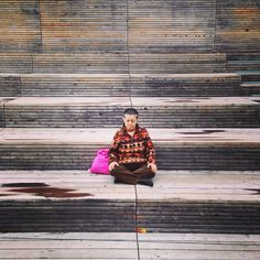 Old Lady is meditating in the High Line in NYC on a stair.