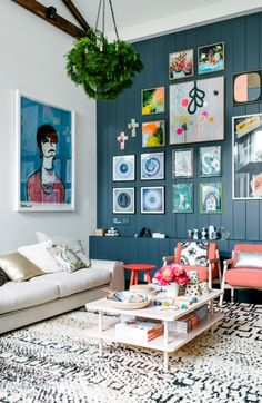 //living room, colorful art pieces, blue wall, table, white couch, golden pillows, pink chairs//