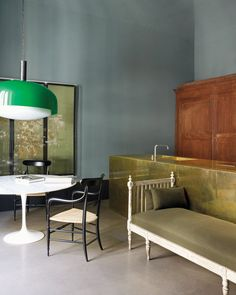 The Dimore Studio designers Britt Moran and Emiliano Salci open their Milan House - A vintage Kartell pendant over a marble Saarinen dining table, reproduction Chiavari chairs and a late 18th century Gustavian daybed in the kitchen