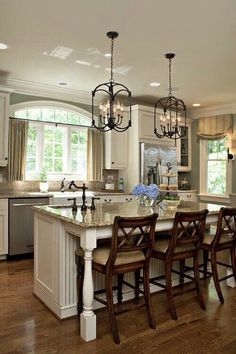Granite countertops, cream cabinets with wood and brown bar stools.