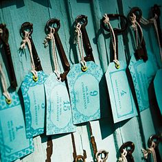 Tags bearing guests' names and table numbers were hung from antique skeleton keys that had been suspended from nails on weathered turquoise doors...with a color change this would work for my wedding.