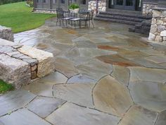 Granite steps and irregular bluestone were used to create this backyard retreat. Natural stone patio. Backyard design. Hardscaping backyard.