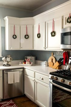 Decorating a kitchen for Christmas. Love the little wreaths on cabinets!