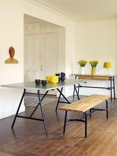 Choć czarne metalowe nogi stołu, ławki i konsoli kojarzą się z ciężkim przemysłowym stylem, dzięki połączeniu z pastelowymi i drewnianymi elementami tworzą przyjemne meble do salonu z jadalnią. Ławka zamiast krzeseł czy taboretów jest praktyczniejsza, bo pomieści więcej osób. Nieco sfatygowana drewniana podłoga dodaje aranżacji szlachetności.