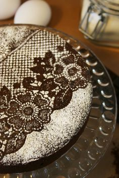 Lay a piece of lace over a cake and sprinkle powdered sugar on it. Remove the lace carefully, and Voila' !