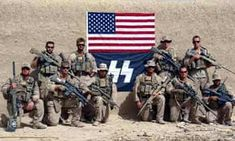 Members of the U.S. Charlie Company, 1st Reconnaissance Battalion in Camp Pendleton, Afghanistan, in front of a flag featuring the Nazi Schutzstaffel (SS) emblem. The photo was taken in September 2010 in Sangin province. Bush Jr, Marine Corps Bases, Camp Lejeune, Camp Pendleton, Military News, Pop Culture References, Confederate Flag, Police Chief, Knights Templar
