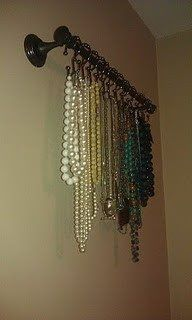 A hand towel rack and shower curtain hangers to organize necklaces and keep them from getting tangled
