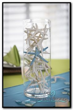 Florida Beach Wedding Decor Ideas- A Simple but Elegant Centerpiece using Starfish. Coloring one of the starfish adds a nice personal touch to tie in with your colors.