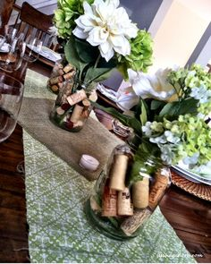 simple centerpieces for casual dinner party, mason jars, flowers and corks on fabric