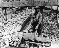 A Cariboo miner sluicing for gold with a rocker box.