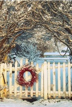 An outdoor wreath on a white picket fence