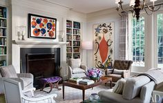 Artworks by Alexander Calder (left) and Joan Miró hang in the living room; the club chairs, sofa, cocktail table, and bench—covered in a Cowtan & Tout velvet—are all by Hickory Chair.