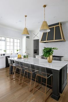 Two Goodman Hanging Lamps light a black kitchen island seating Gabby Home King Barstools facing a gold and black range hood mounted to white linear backsplash tiles over a stainless steel dual range.