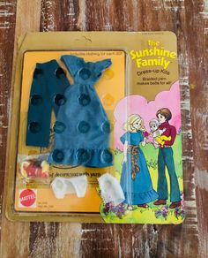 This 1975 Mattel Sunshine Family fashion pack includes a dress for mom Stephie, a sweater and pants for dad Steve, a bonnet and top for baby Sweets, yarn and an idea book. Children could braid colorful belts with the yarn! #SunshineFamily #BabySweets