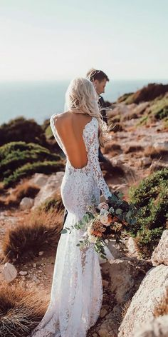 a backless lace applique wedding dress with long sleeves and a small train is very sexy and chic