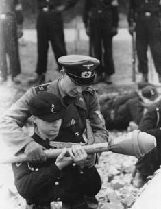 A German noncommissioned officer teaches a member of the Hitler Youth the  skills of firing a Panzerfaust 114e8a5ba437
