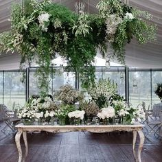 Linda mesa de doces decoraca apenas com verdes e flores brancas.