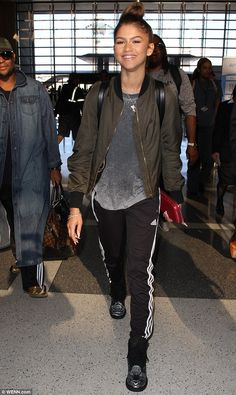 Travelling in style: The 19-year-old opted for a comfy outfit, donning a grey T-shirt under a khaki green bomber jacket with a ribbed collar and cuffs with black exercise trousers with white stripes down the sides