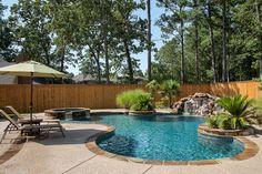 Bossier City Pool Design, Shreveport Pool Construction - natural-boulder-waterfall-spa-tanning-ledge-Cool-Deck-stone-planter-ocean-blue-pebble-sheen-umbrella-