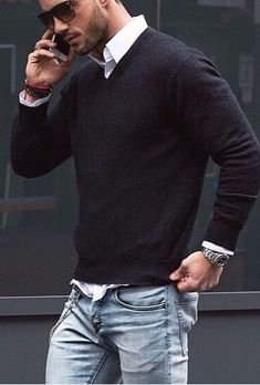 Pairing a black v-neck pullover with light blue jeans is a comfortable option for running errands in the city.